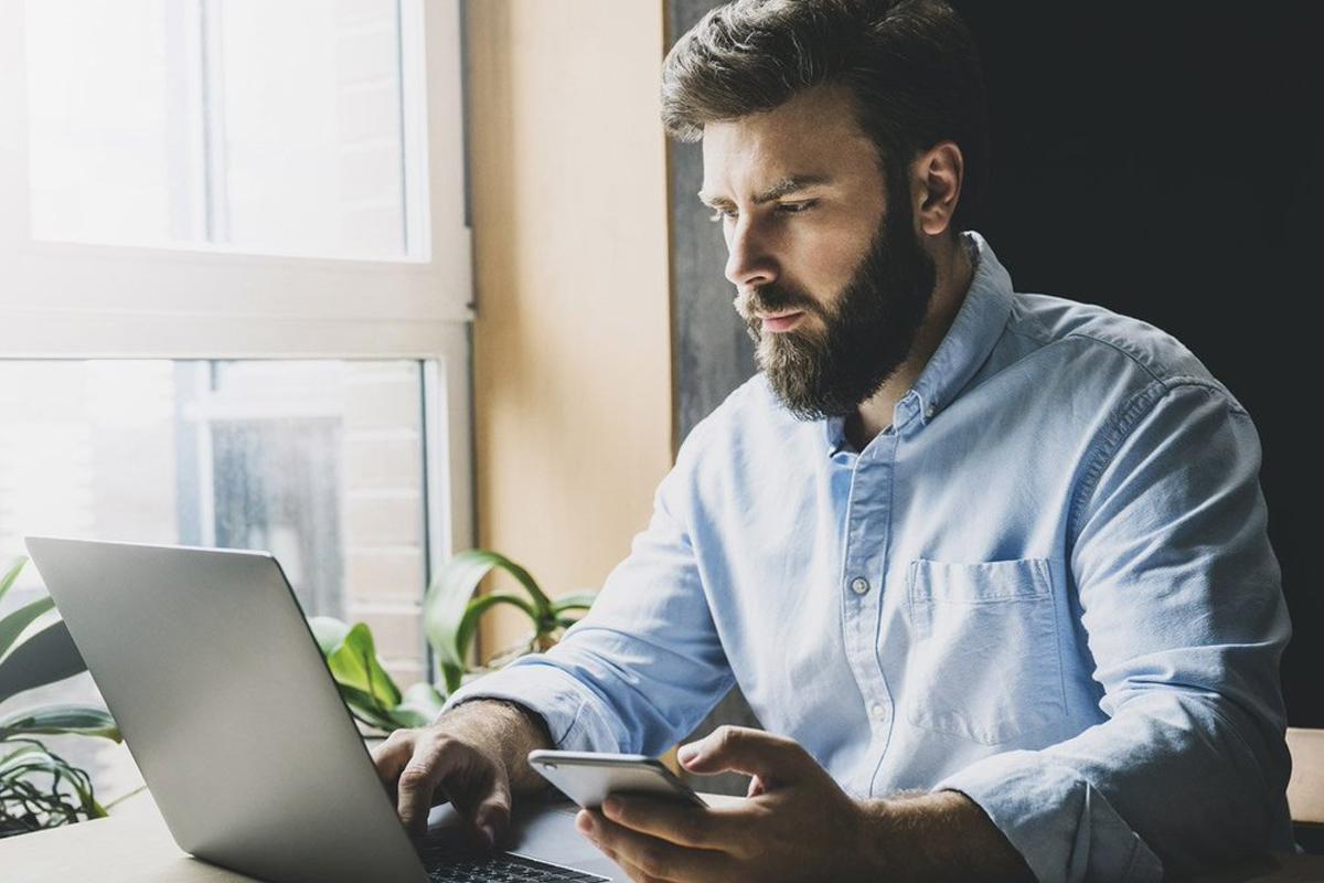 Man analyzing computer and phone